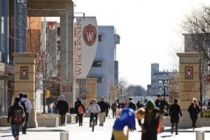 On a sunny December day, pedestrians walk past the University Square complex and Student Services Tower at 333 East Campus Mall at the University of Wisconsin-Madison on Dec. 4, 2012. (Photo by Bryce Richter / UW-Madison)